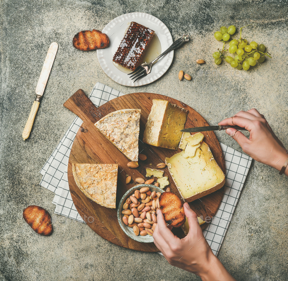 Cheese platter with female hands reaching to food, top view - Stock Photo - Images