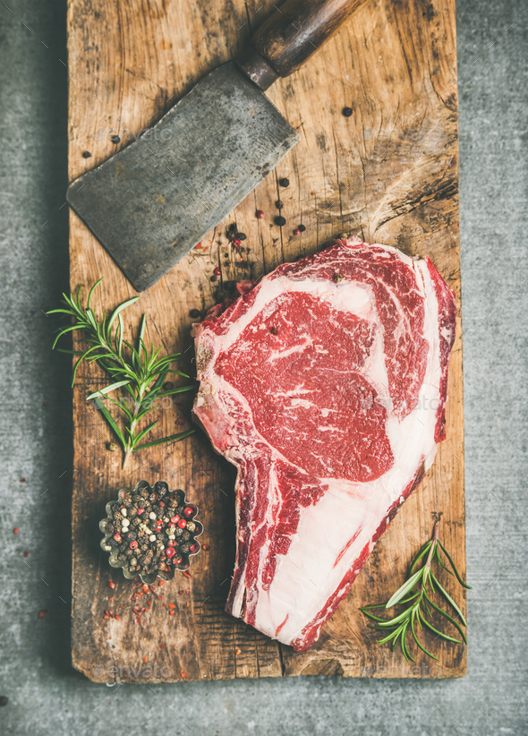 Raw prime beef meat dry-aged steak rib-eye and chopping knife - Stock Photo - Images