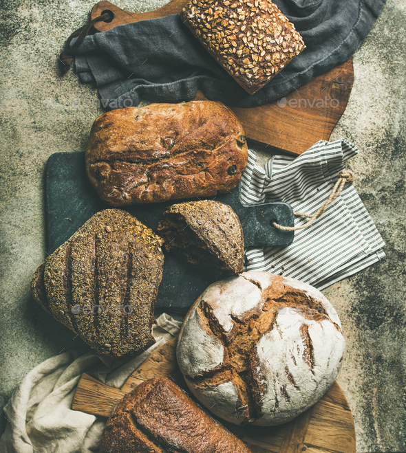 Flat-lay of various bread loaves on grey background, top view - Stock Photo - Images