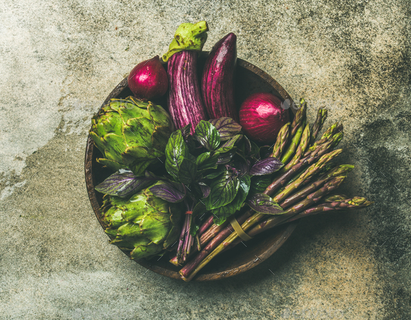 Flat-lay of green and purple vegetables on plate, grey background - Stock Photo - Images