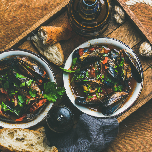 Belgian boiled mussels in tomato sauce with parsley in tray - Stock Photo - Images