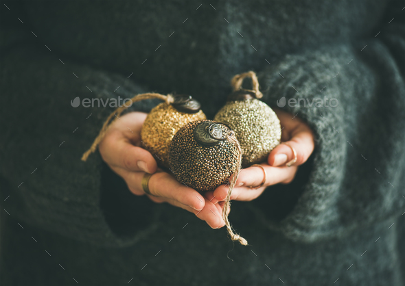 Woman in sweater holding golden and silver balls in hands - Stock Photo - Images