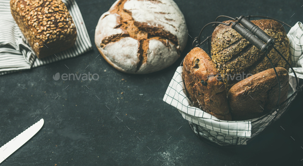 Various bread loaves over black background, copy space, horizontal composition - Stock Photo - Images