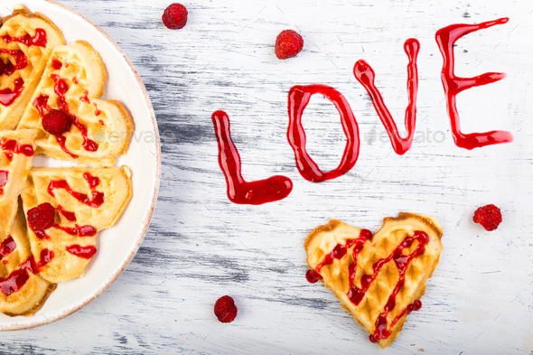 Belgian heart shaped waffle on white background. Word love made by jam. - Stock Photo - Images