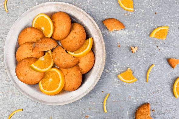 Cookies and orange citrus fruit on metal plate on grey background. Flat lay - Stock Photo - Images