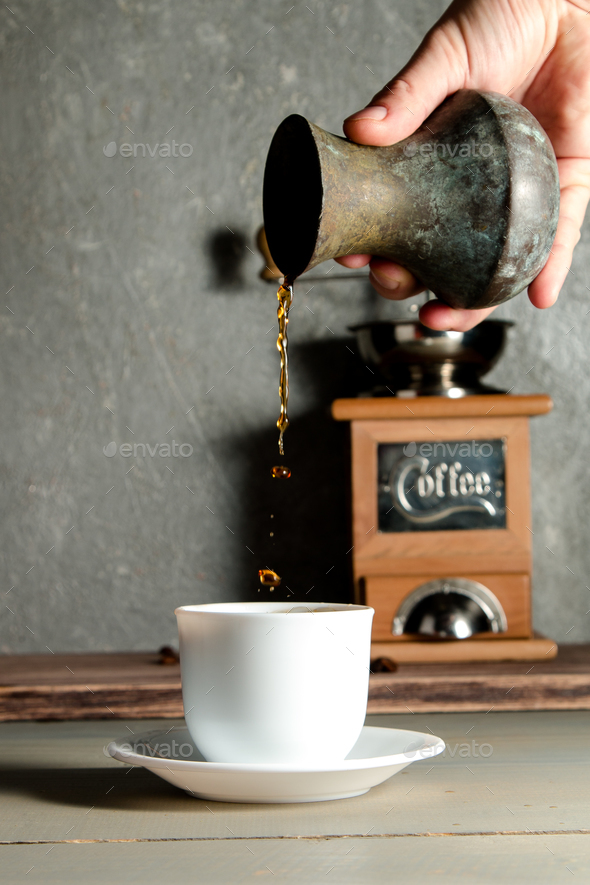 Men Hand Pouring a Cup of Coffee Creating Splash on Wooden Background. - Stock Photo - Images