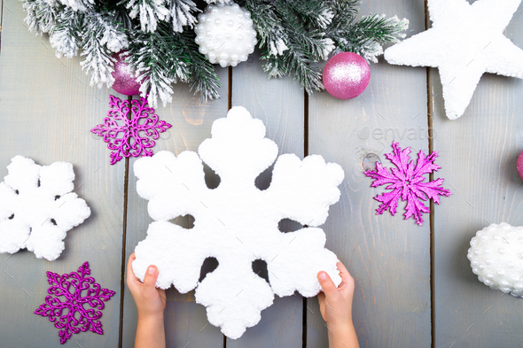 Christmas decoration. Child hand with decorative snowlake. Top view. - Stock Photo - Images