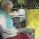 Senior Woman Reads Book in Park - VideoHive Item for Sale