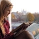 Beautiful Young Woman Reads Old Book Near the Window - VideoHive Item for Sale