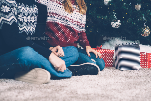 Crop couple sitting on carpet with presents - Stock Photo - Images
