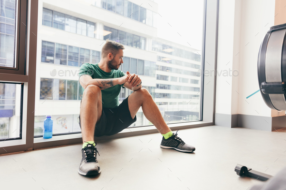 Young man having a break in his gym workout. - Stock Photo - Images