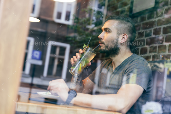 Man drinking cold fit beverage in a cafe. - Stock Photo - Images
