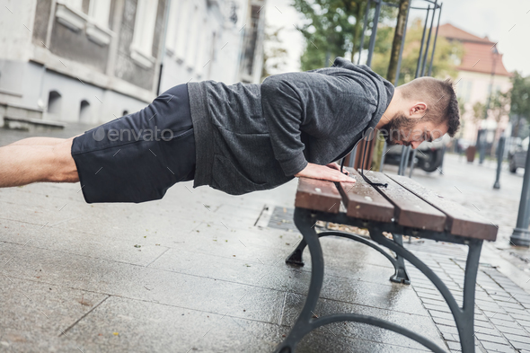Man doing push-ups on a bench. - Stock Photo - Images