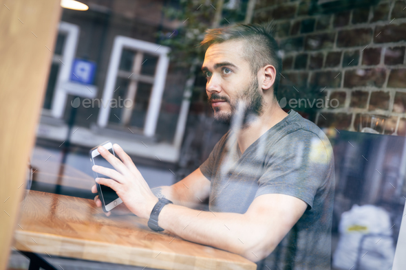 Man in a cafe looking by the window. - Stock Photo - Images