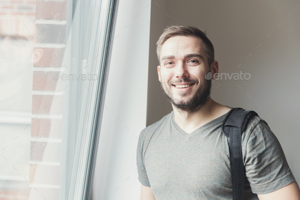 Young man smiling next to the window. - Stock Photo - Images