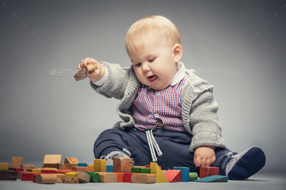 Toddler boy playing with building blocks. - Stock Photo - Images