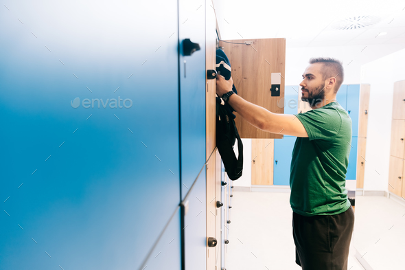 Man packing his gym bag into a blue locker - Stock Photo - Images