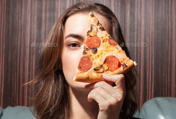 female face near pizza slice - Stock Photo - Images