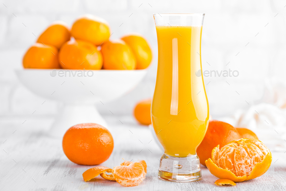 Tangerines, peeled tangerines and tangerine juice in glass. Mandarine juice. - Stock Photo - Images