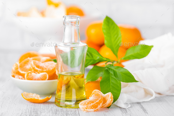 Tangerines with leaves and bottle of essential citrus oil on a white background - Stock Photo - Images