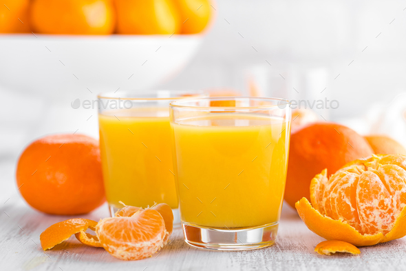 Tangerines, peeled tangerines and tangerine juice in glass. Mandarine juice. - Stock Photo - Images