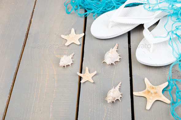Seashells and white flip flops grey wooden background. Flat lay. - Stock Photo - Images