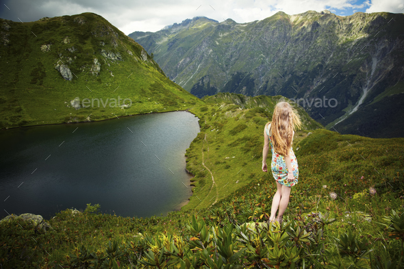 Beautiful young woman with red hair standing on a rock - Stock Photo - Images