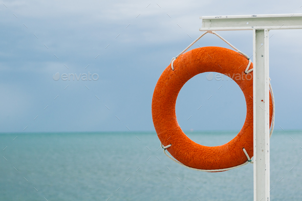 orange lifebuoy on the sea coast - Stock Photo - Images
