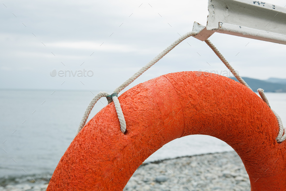 orange lifebuoy on the sea coast - Stock Photo - Images