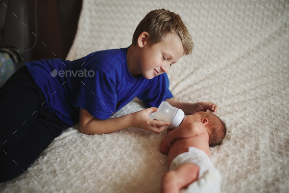 boy feeding newborn baby with bottle of milk - Stock Photo - Images