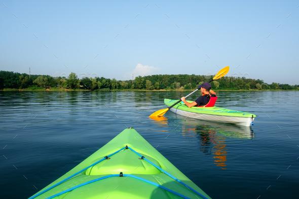Boy in life jacket on green kayak - Stock Photo - Images