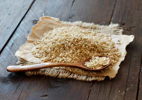 Pile of Brown rice with a wooden spoon - Stock Photo - Images