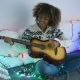 Cheerful Woman Playing Guitar in Garland Lights