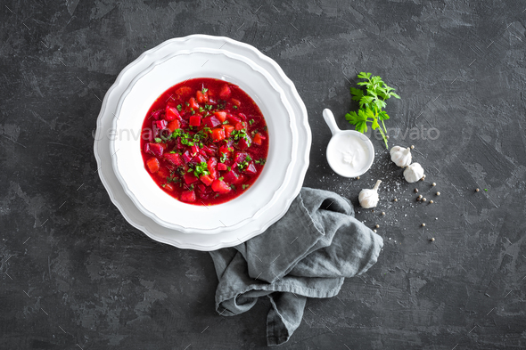 Vegetarian hot diet beetroot soup with vegetables on plate, top view, dark background - Stock Photo - Images