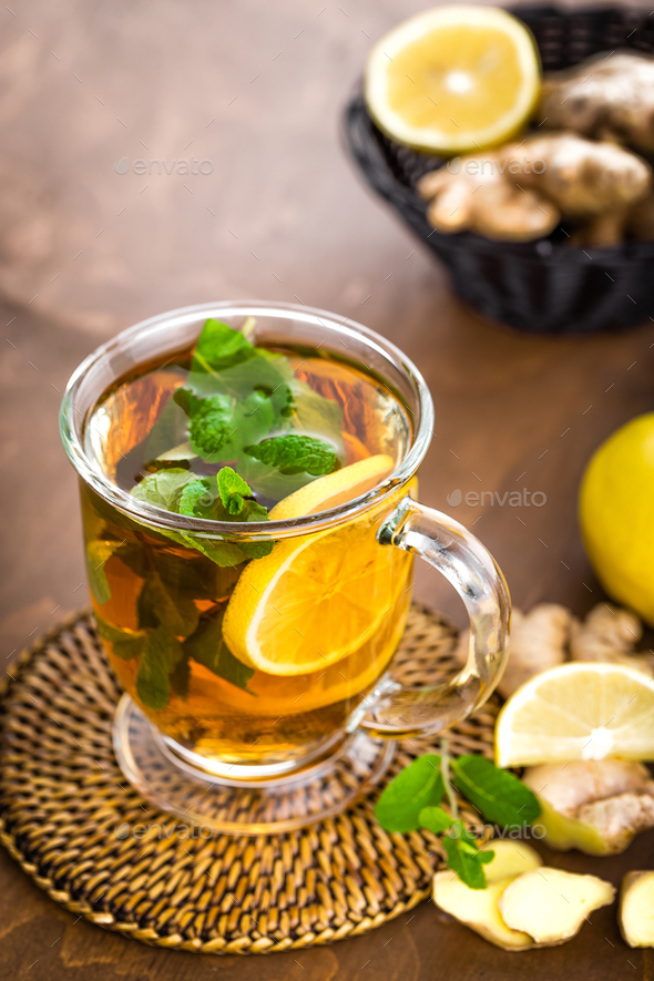 Hot herbal tea with fresh lemon, ginger and mint leaves on brown background, closeup - Stock Photo - Images