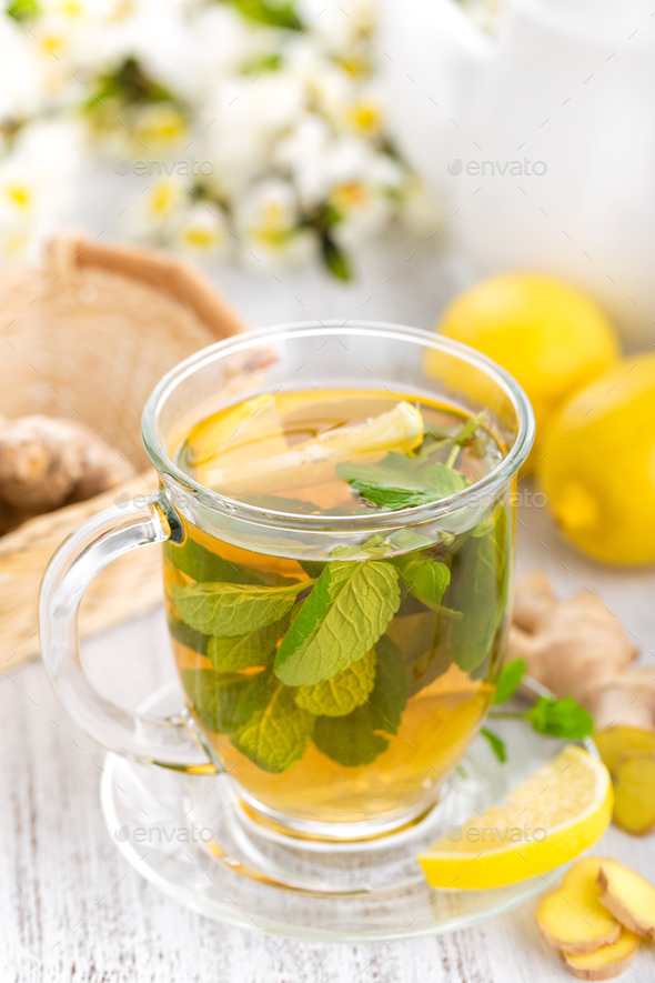 Flavored herbal tea with fresh lemon, ginger and mint leaves on white background, closeup - Stock Photo - Images