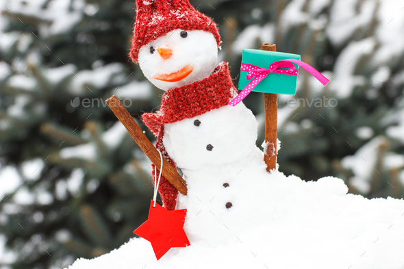 Snowman with gift for Christmas or Valentine - Stock Photo - Images