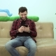 Charismatic Man Sitting on Sofa and Looks on His Phone , He Is Smiling and Are Happy
