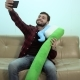 Smiling Man Take a Selfie with a Teeth Brush Sitting on Sofa - VideoHive Item for Sale