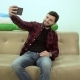 Happy Smiling Man Taking Selfie with His Phone Sitting on the Sofa - VideoHive Item for Sale