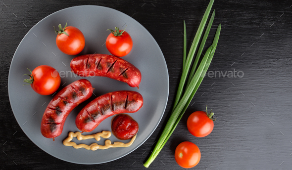 Fried sausages on a plate with tomatoes and ketchup - Stock Photo - Images