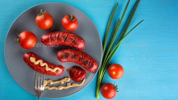 Nutritional sausages strung on fork with red tomatoes on plate - Stock Photo - Images