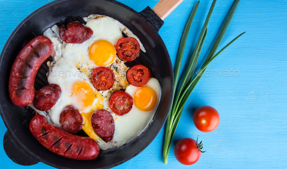Fried sausages with eggs in cast-iron frying pan - Stock Photo - Images