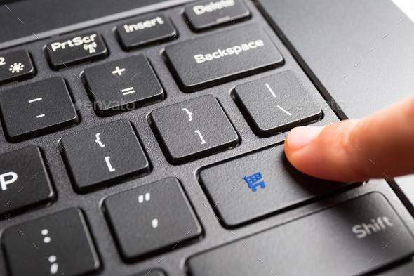 finger pressing shopping cart key - Stock Photo - Images