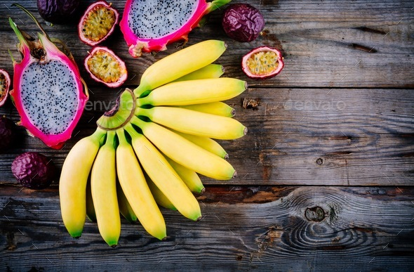 Mix of tropical fruits with banana, passion fruit and dragon fruit on a wooden background. - Stock Photo - Images