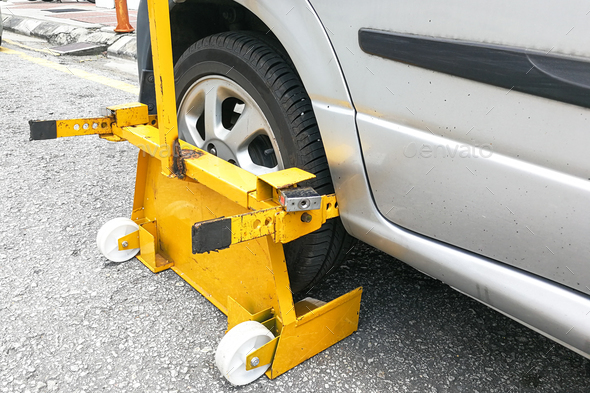 Car wheel clamp on street for illegal parking - Stock Photo - Images