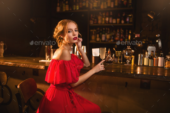 Portrait of woman in red dress at the bar counter - Stock Photo - Images