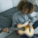 Relaxed Woman Playing Guitar at Home
