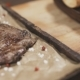 Chef Is Finishing Serving Beef Steak with Pepper, Rosemary and Salt on Wooden Board - VideoHive Item for Sale