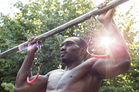 Athletic black man posing in a city park - Stock Photo - Images